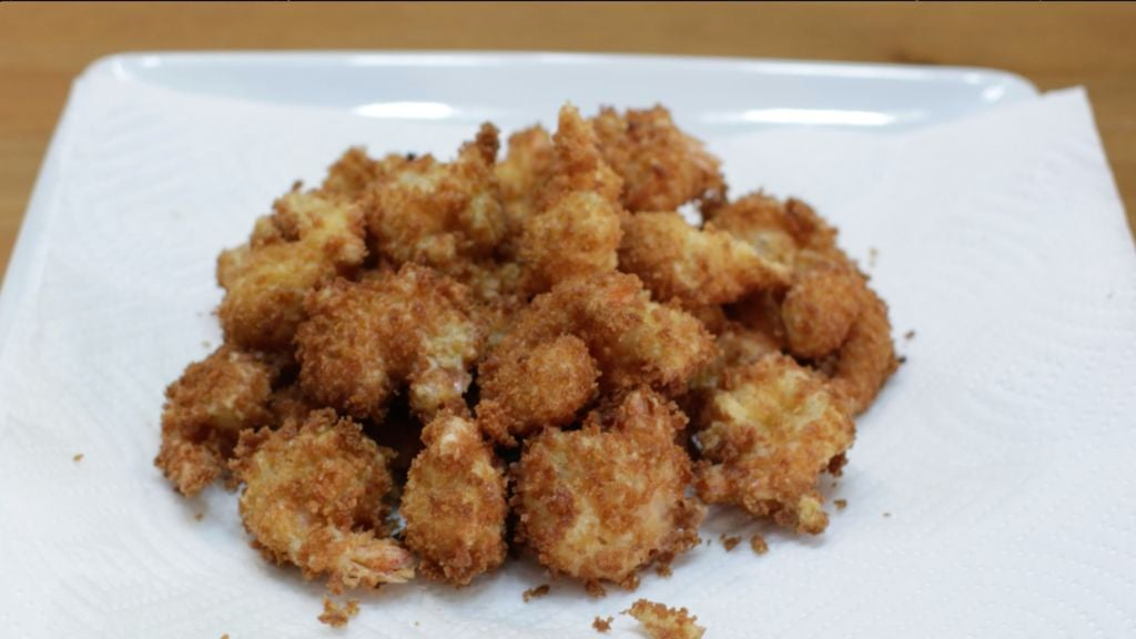 Pile of easy crispy fried shrimp on a white plate lined with white paper towel.