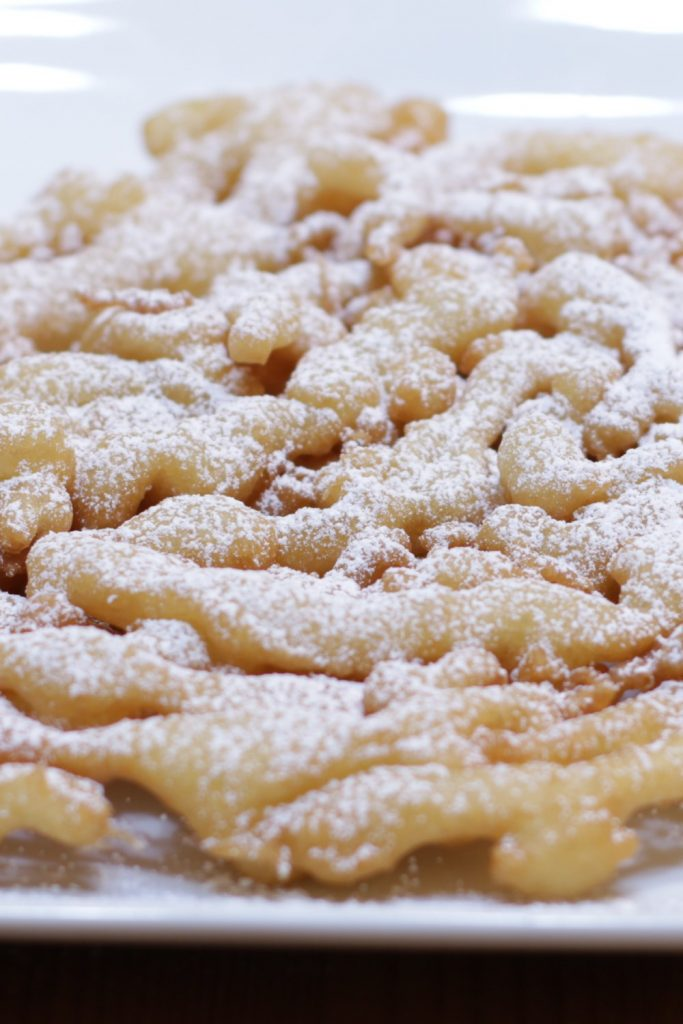 Funnel cake covered with powdered sugar on top of a white plate.