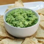 Homemade guacamole recipe dip in a white bowl with tortilla chips on a white plate