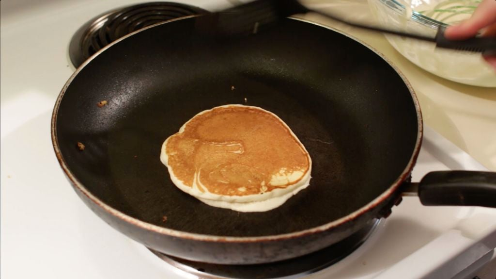 Easy homemade fluffy pancake in a black skillet on a white stovetop.