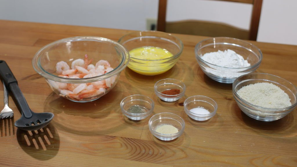 Shrimp, eggs, flour, bread crumbs, and spices in bowls on a wooden table.