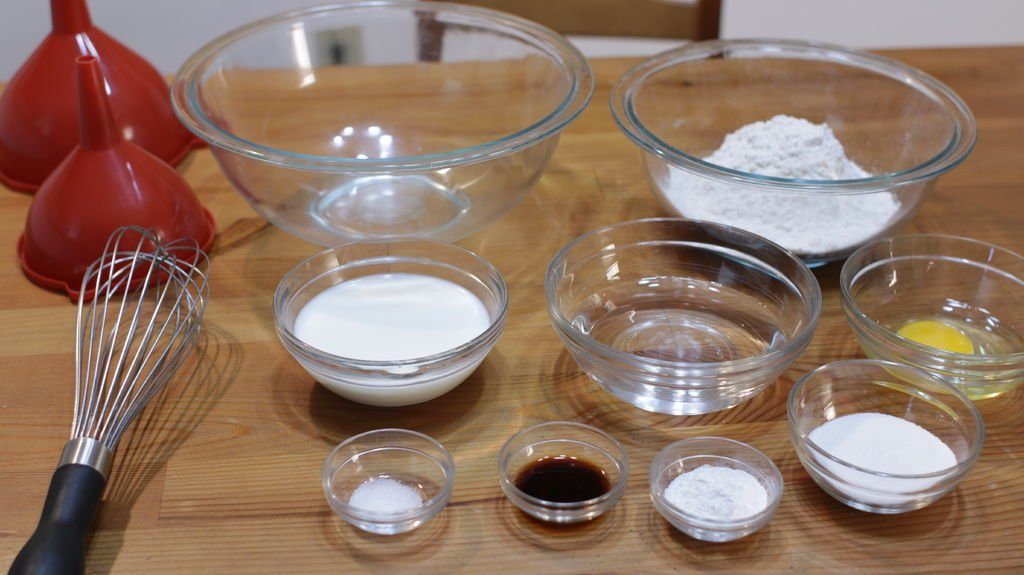 Several ingredients like flour, egg, water, milk, etc. in glass bowls on top of a wooden table.