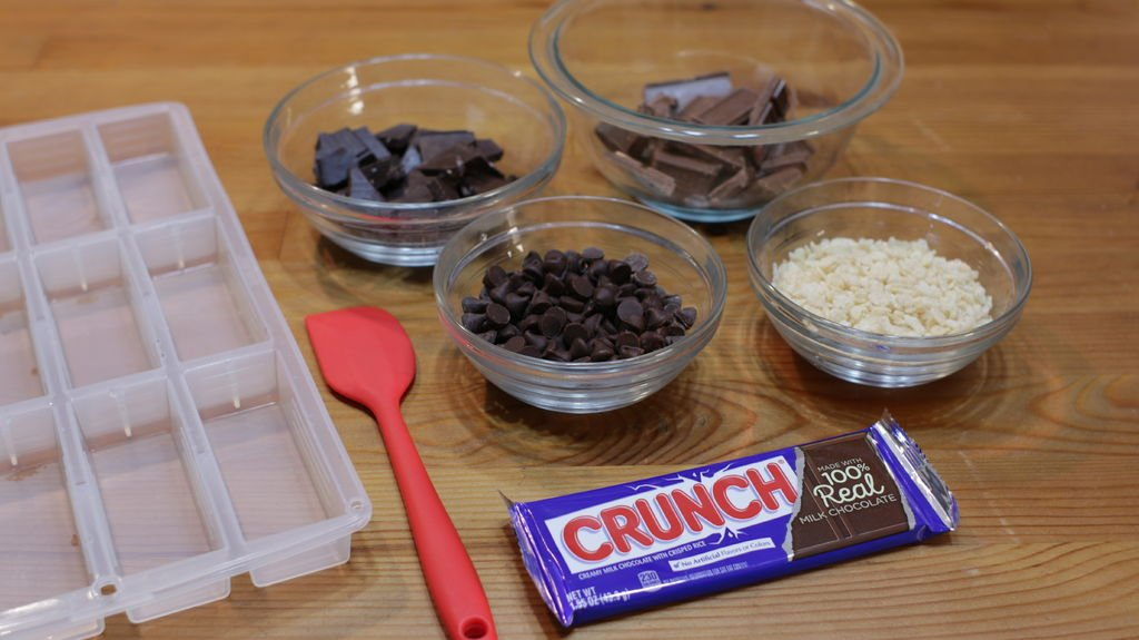 Different kinds of chocolate in bowls with rice krispies and a crunch bar in its wrapper.