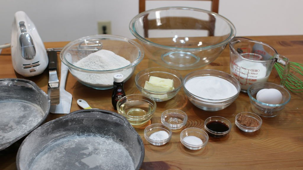 Cake ingredients in glass bowls on top of a wooden table.