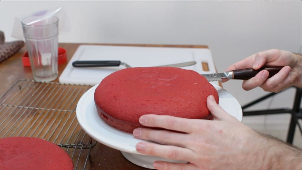 Hand slicing the top off a cake half with a bread knife.