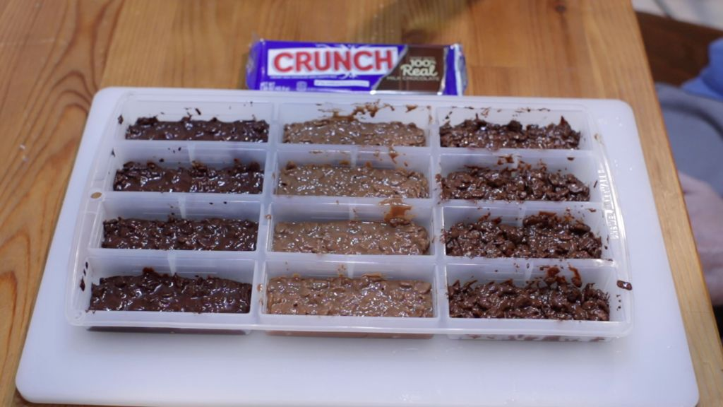 12 homemade crunch bars in a silicone candy bar mold ready to go into the fridge.