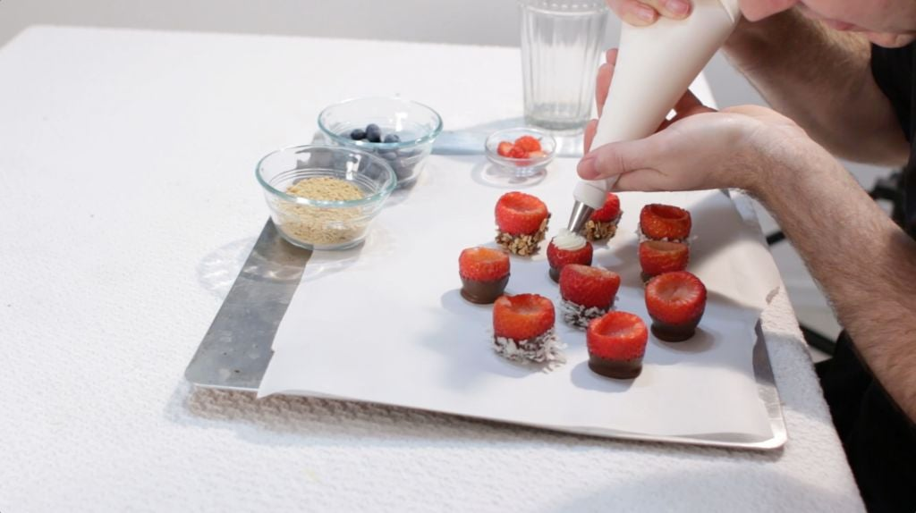 Hand stuffing strawberries with cheesecake filling in a piping bag.