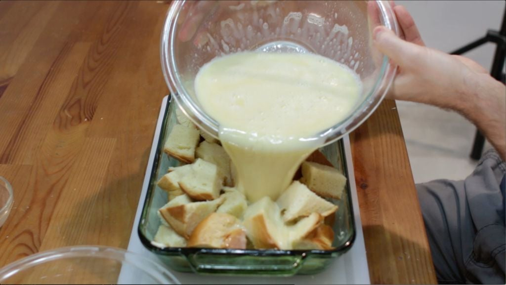 Hand pouring custard over bread chunks in a green glass baking sheet.