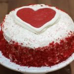 Red velvet cake with heart on top sitting on a white cake pedestal.