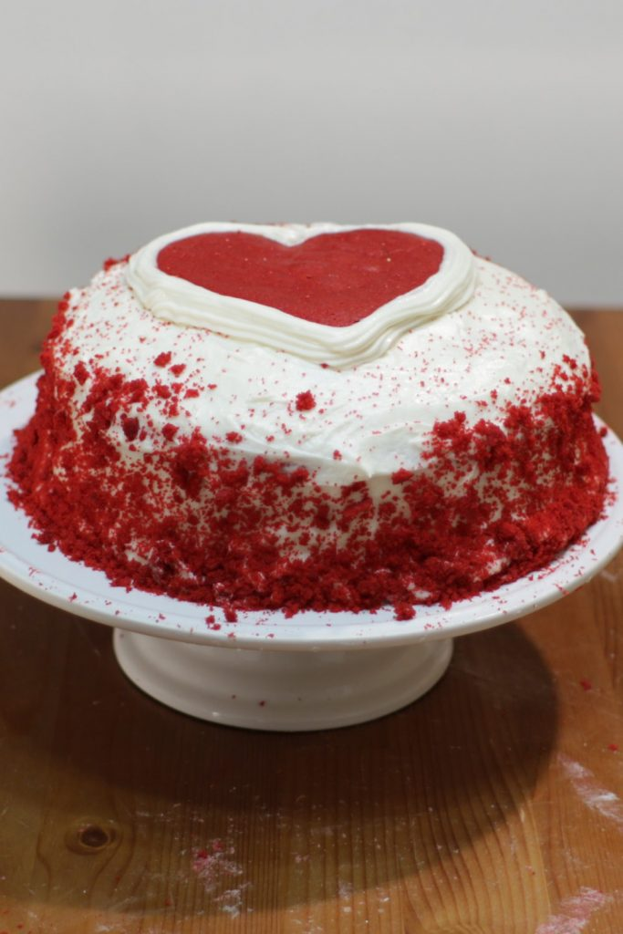 Finished homemade red velvet cake on top of a white cake pedestal on top of a wooden table.