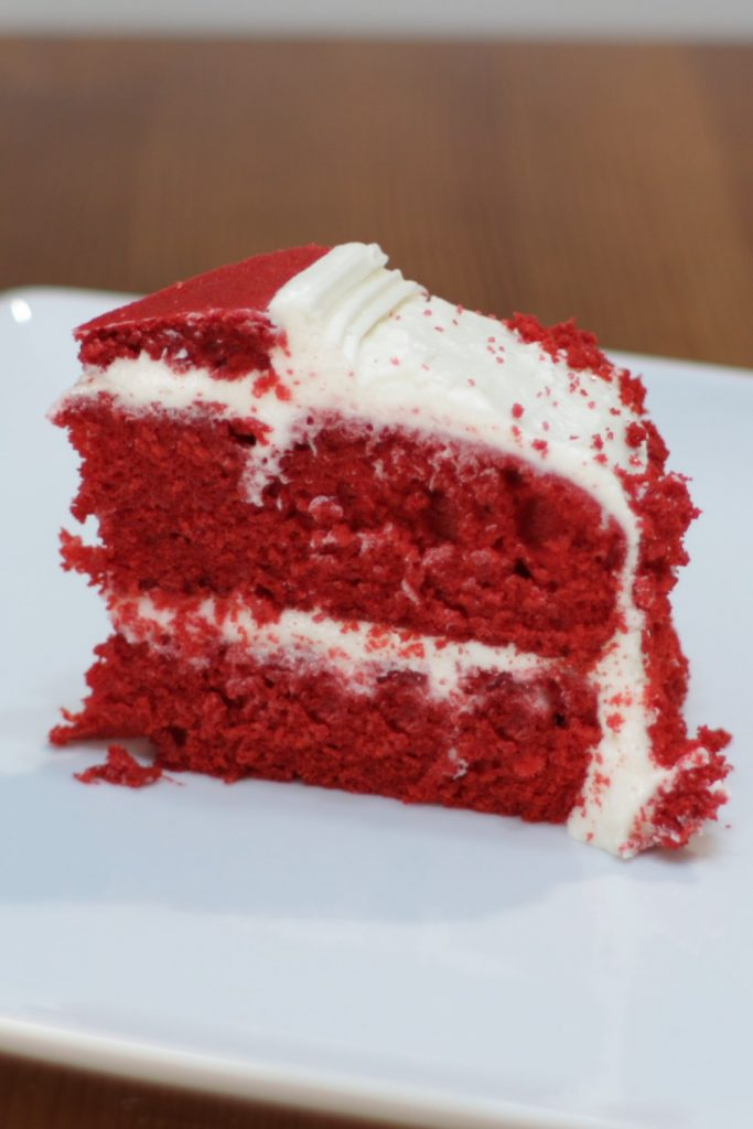 Slice of red velvet cake on a white plate on a wooden table.