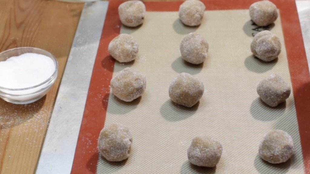 Rolled balls of molasses cookie dough on a sheet pan lined with a silicone baking mat