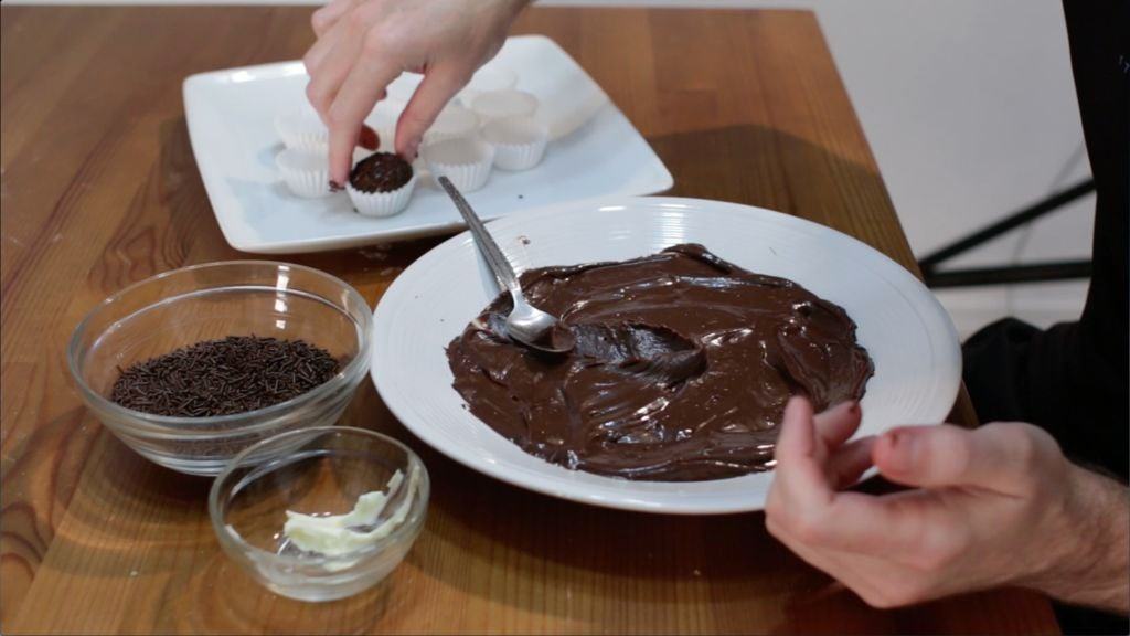 Hand making brigadeiro balls and placing them on a white plate