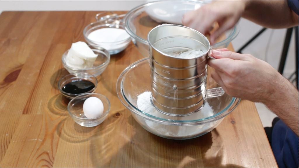 Hand sifting dry cookies ingredients into a large glass bowl