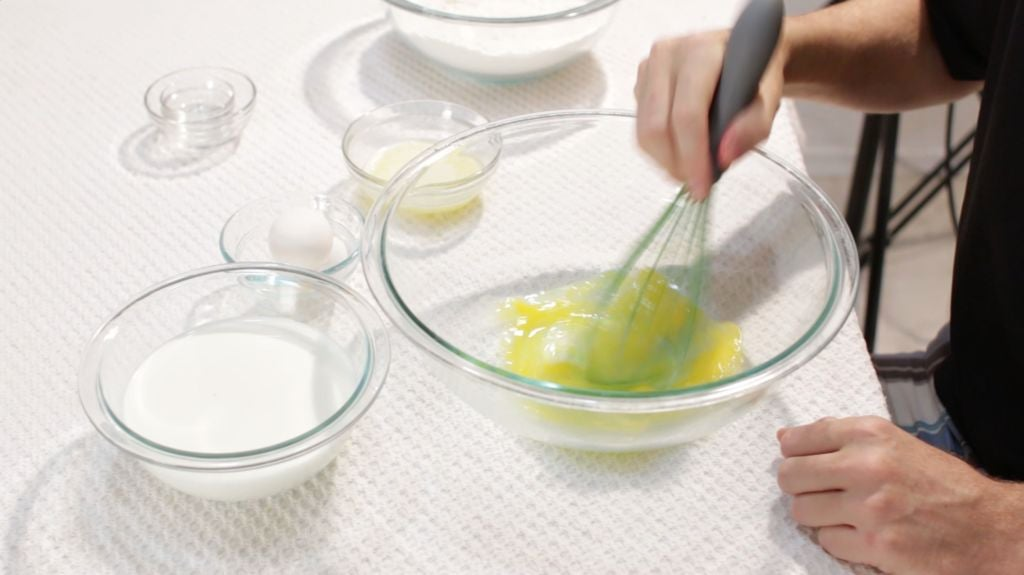 Hand whisking eggs in a large glass bowl.