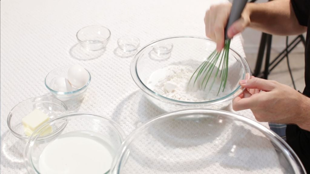 Hand whisking dry pancake ingredients in a medium glass bowl.