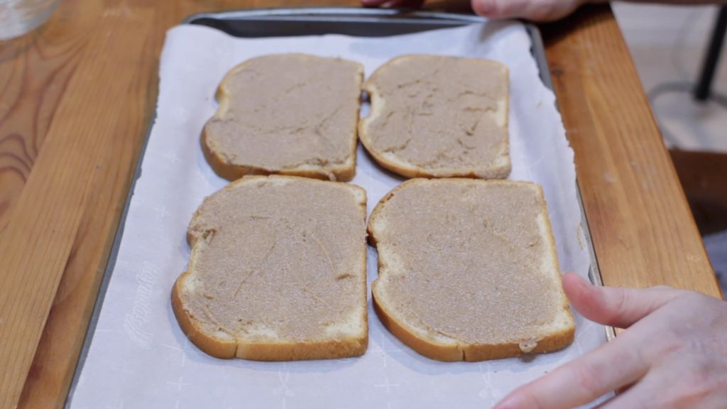 Four slices of white bread with cinnamon toast paste spread out on top laying on a sheet pan lined with parchment paper.