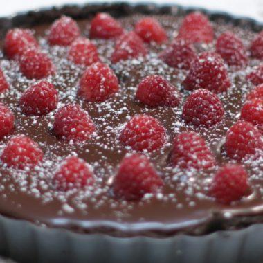 Chocolate raspberry tart on a white table