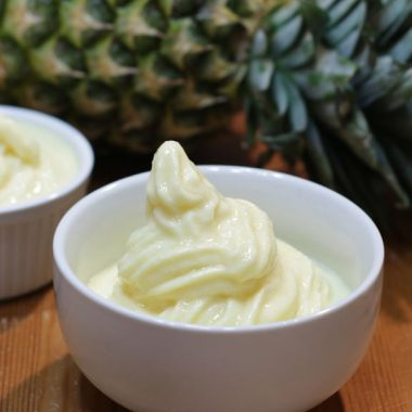 Two white cups of Disney Dole Whip next to a pineapple