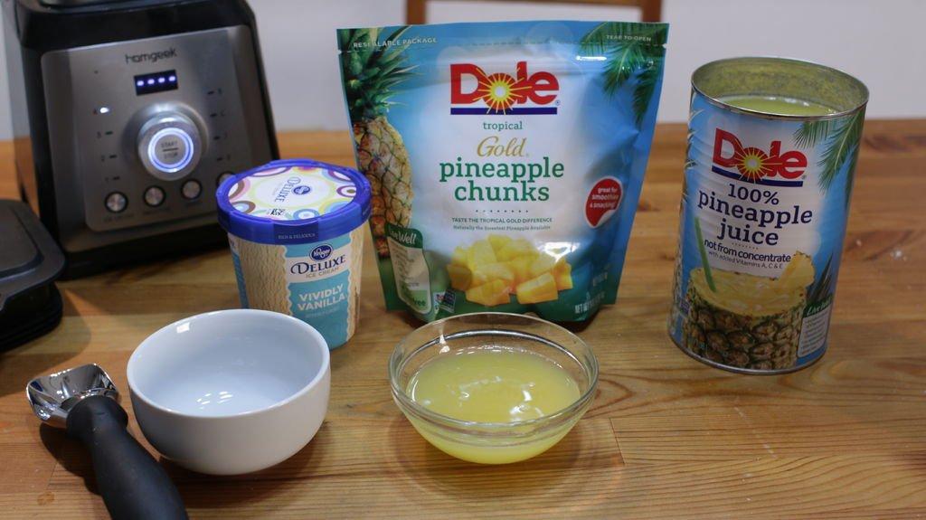 Dole pineapple chunks, juice, and vanilla ice cream on a table.