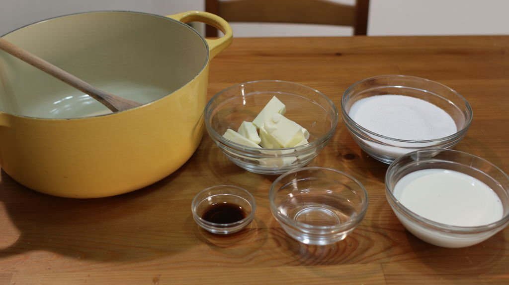 Several ingredients in glass bowls on top of a wooden table. There is butter, sugar, cream, water, and vanilla extract.