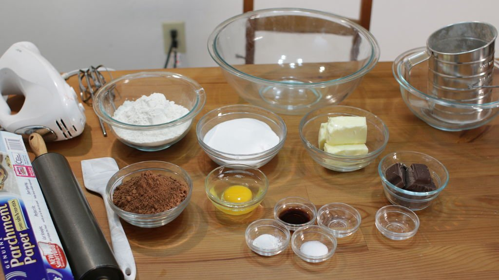 Several ingredients in glass bowls on top of a wooden table, including chocolate, butter, sugar, cocoa powder, etc.