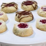 several round shortbread cookies on a white cake pedestal