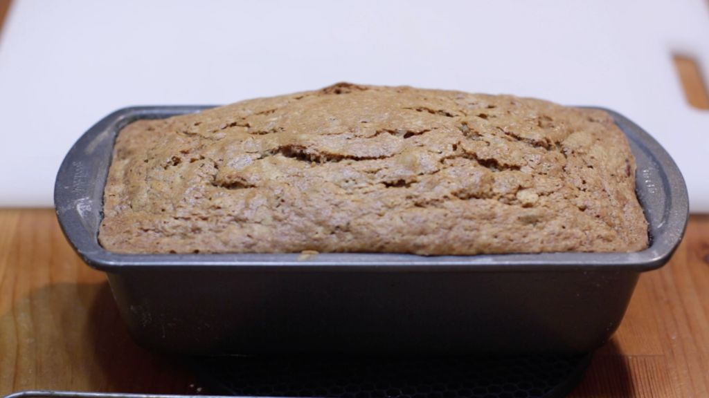 Freshly baked zucchini bread in a bread loaf pan on a wooden table.