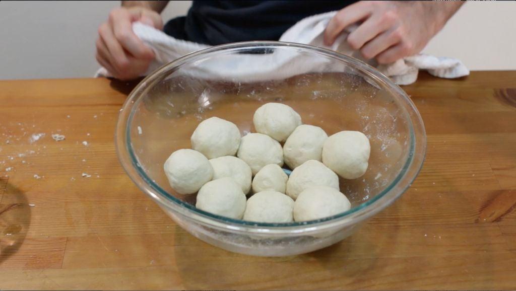 11 balls of flour tortillas dough in a large glass bowl