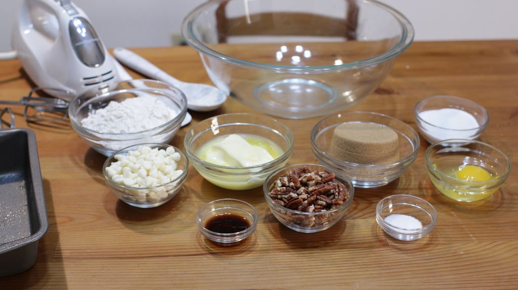 Several blondie ingredients in glass bowls on top of a wooden table.