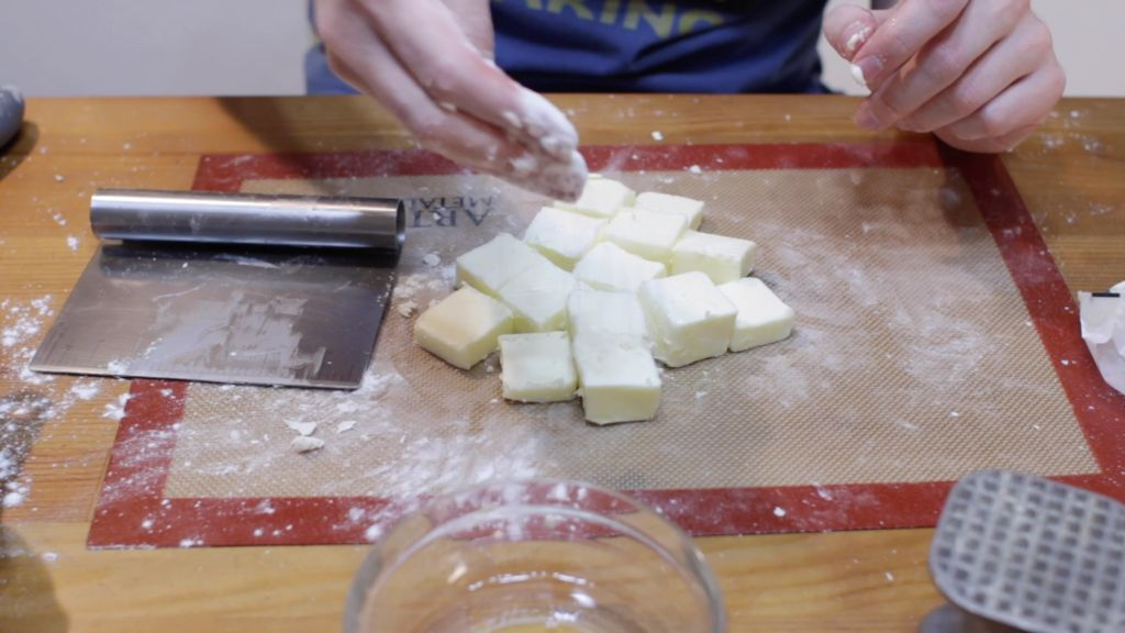 Hand dusting the tops of butter chunks with flour.