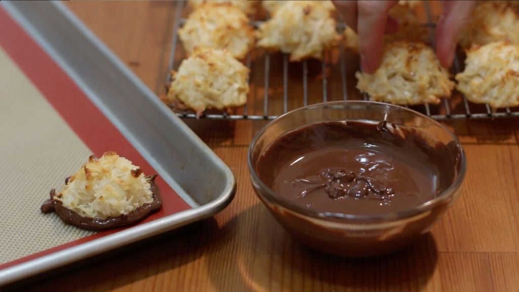 Glass bowl of melted chocolate next to coconut macaroons.