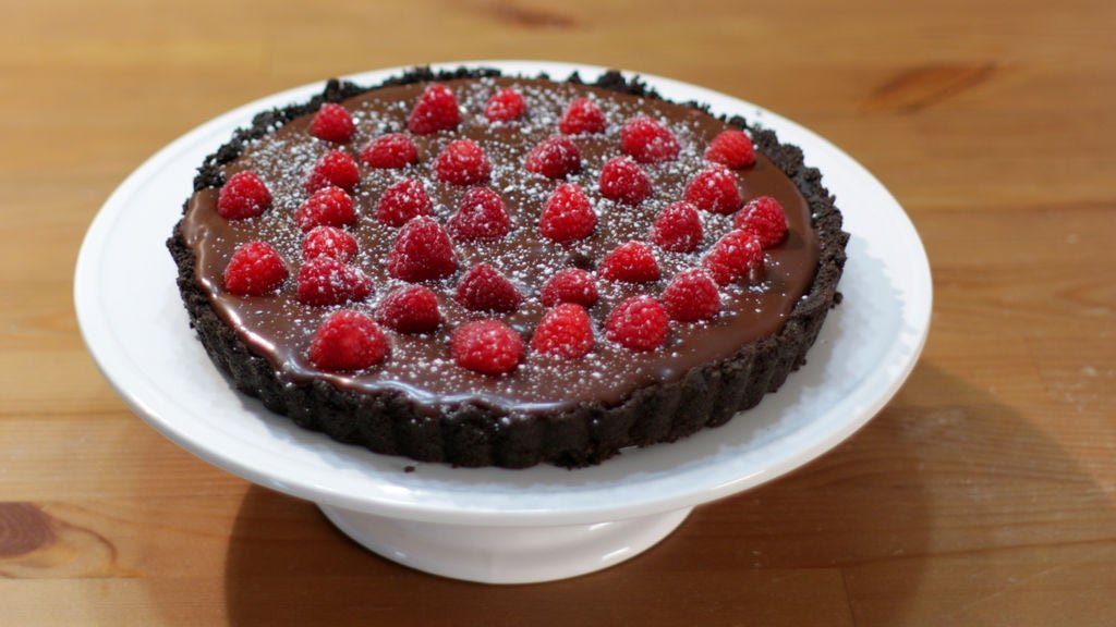Complete homemade chocolate raspberry tart on a white cake pedestal.