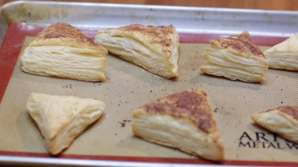 Homemade puff pastry baked with cinnamon and sugar on a sheet pan with silicone mat.