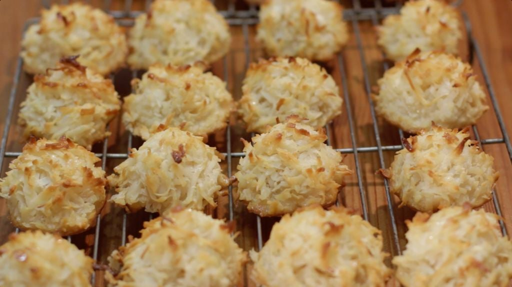 Baked coconut macaroons on a wire rack on a wooden table.