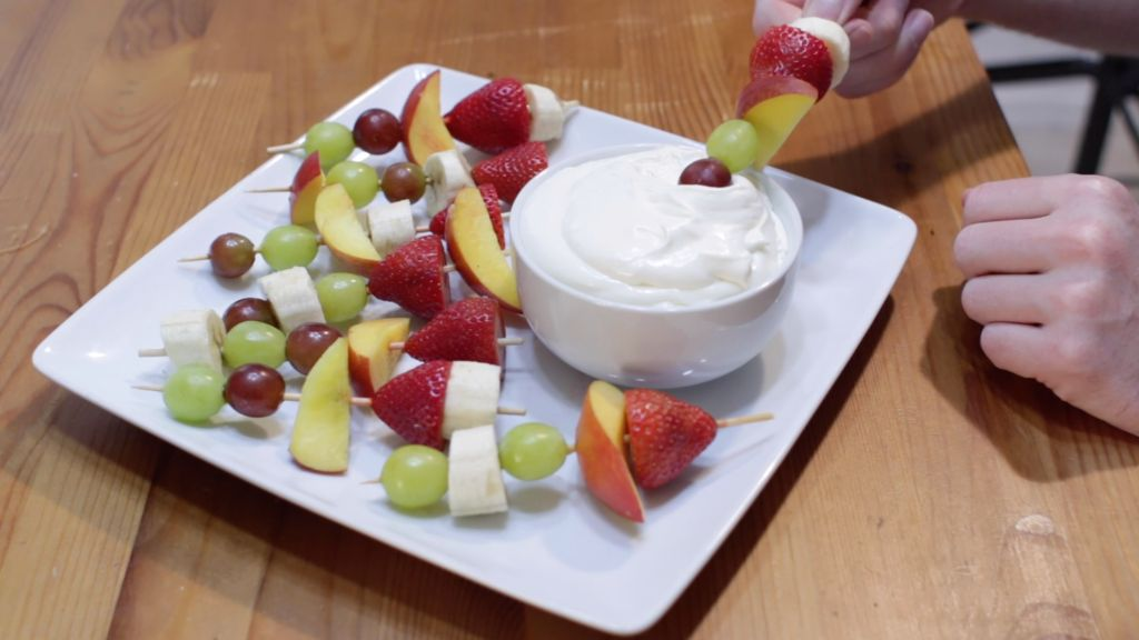 Homemade fruit dip in a white bowl on a plate with fruit kebabs
