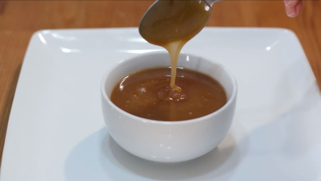 Spoon dripping caramel sauce into a white bowl on a white plate.
