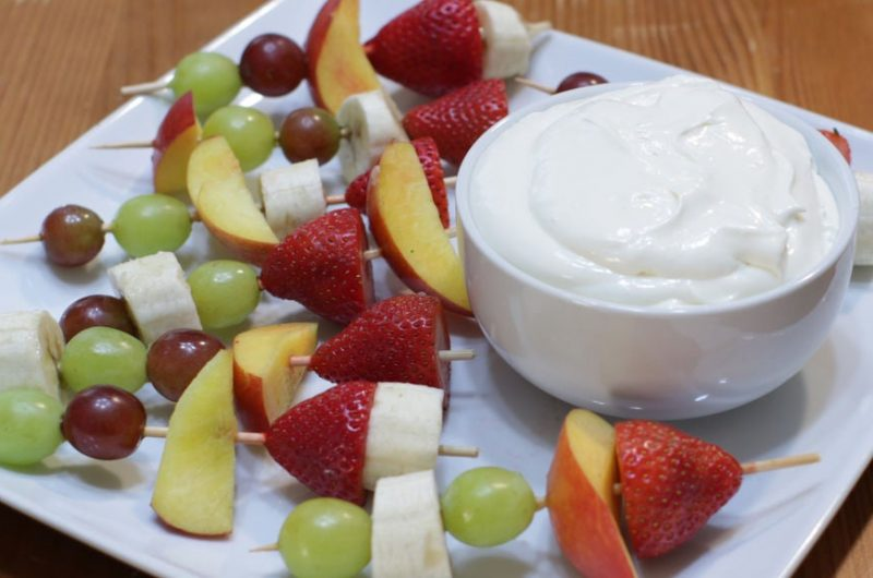 Easy homemade fruit dip in a bowl on a plate with fruit kebabs