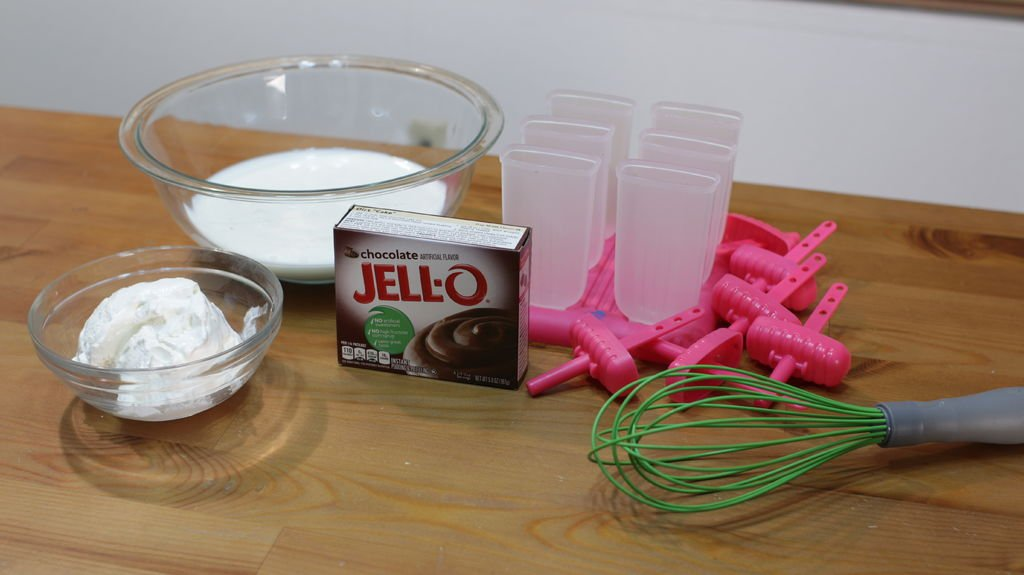 Jello chocolate pudding mix, cool whip, milk and popsicle molds on a wooden table.