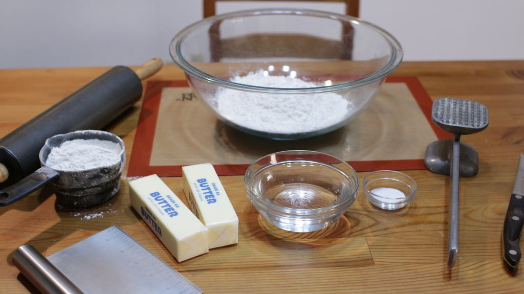 A large glass bowl with flour and a few other bowls with butter and water on a table.