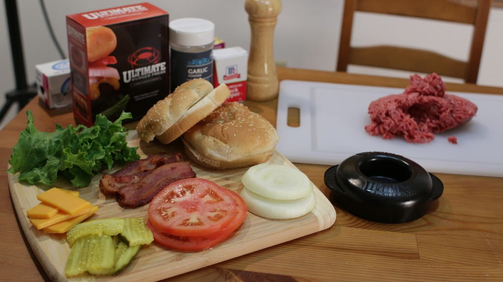 Hamburger ingredients on a wooden table including ground beef, onions, tomato, buns, bacon, pickles, cheese, and lettuce.