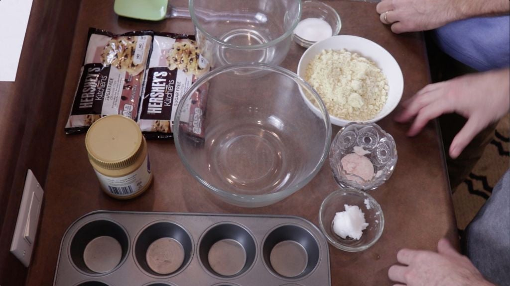 Several ingredients like chocolate chips, coconut oil, salt, almond flour, and peanut butter on a counter.