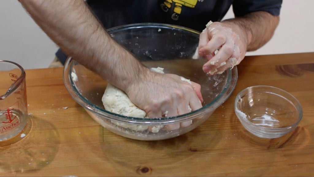 Hand kneading soft flour tortillas dough in a large bowl.