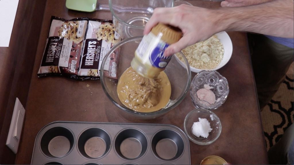 Hand adding peanut butter to a bowl.