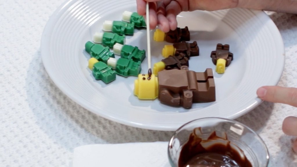 Hand with bamboo skewer painting on a chocolate face to the lego figure