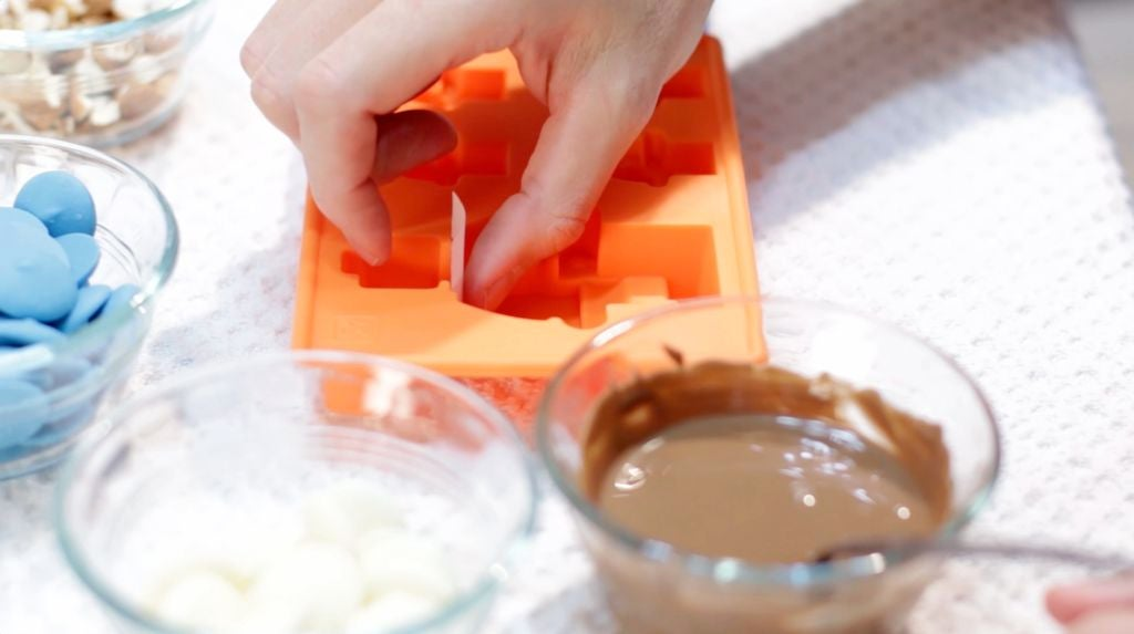 Hand placing a small piece of parchment paper in a lego figure mold.