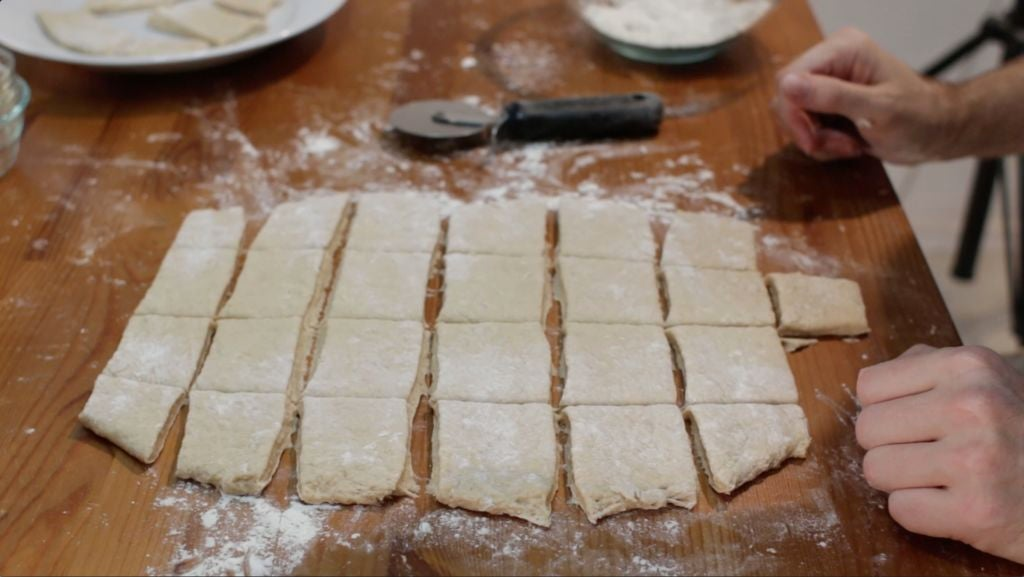 Rolled out beignets dough cut into squares.