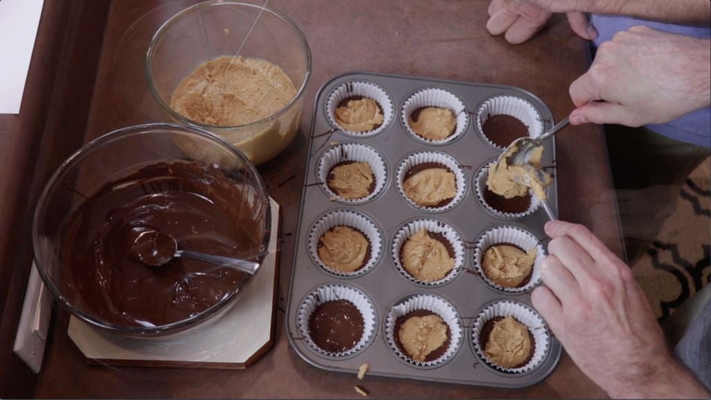 Hand spooning in peanut butter mixture into muffin cups with chocolate.