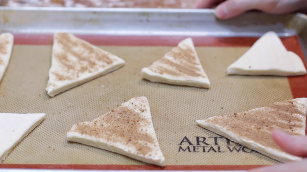 Puff pastry triangles with butter and cinnamon and sugar on top.