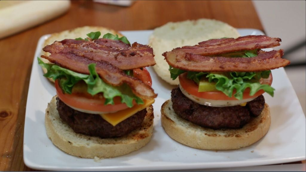 Two juicy loaded hamburgers on a white plate.